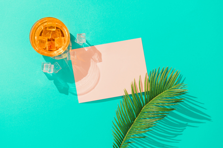 Tropical cocktail with ice cubes, palm leaf  and pink paper card note on vivid blue background. Minimal summer drink composition. Flat lay.