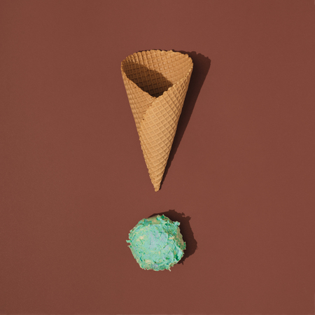 Ice cream cone  with scoop of ice cream on brown background. Minimal summer food concept. Flat lay.