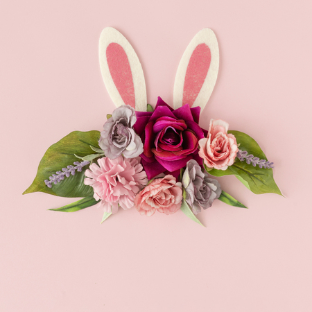 Bunny rabbit ears with spring flowers and leaves onpastel pink background. Happy Easter minimal concept. Flat lay. Imagens