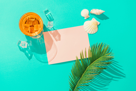 Tropical cocktail with ice cubes, palm leaf, sea shells and pink paper card note on vivid blue background. Minimal summer drink composition. Flat lay. Imagens