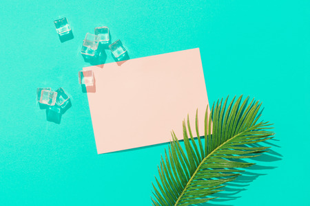 Tropical pal leaf with ice cubes and pink paper card note on vivid blue background. Minimal summer composition. Flat lay.
