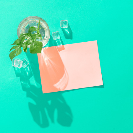 Tropical cocktail with ice cubes and pink paper card note on vivid blue background. Minimal summer drink composition. Flat lay. Imagens