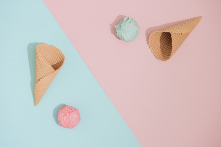 Ice cream cones  with scoops of ice cream on pastel pink and blue background. Minimal summer food concept. Flat lay.