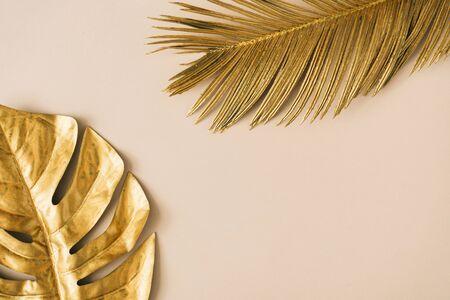 베이지색 배경에 황금색 열대 잎과 야자수로 만든 창의적인 레이아웃입니다. 복사 공간이 있는 최소한의 여름 이국적인 개념입니다. 테두리 배열 배경입니다.