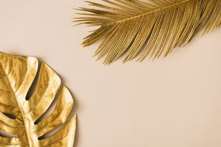 Creative layout made of golden tropical leaves and palms on beige background. Minimal summer exotic concept with copy space. Border arrangement background. Foto de archivo