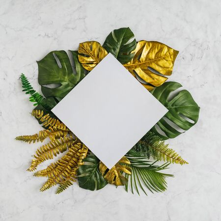 Top view of green and gold tropical leaves on white marble background. Flat lay. Minimal summer concept with palm tree leaves. Creative copy space. Stock fotó - 127507180