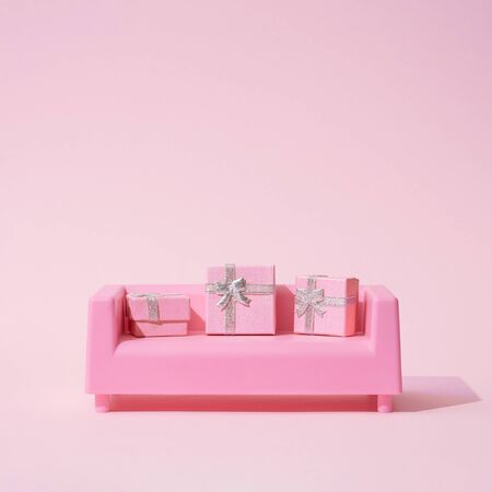 Christmas composition. Pink sofa, with presents on pink background. Christmas holidays, new year minimal concept. Stock Photo