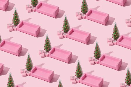 Christmas composition. Pink sofa, Christmas tree with presents on pink background. Winter holidays, new year minimal concept.