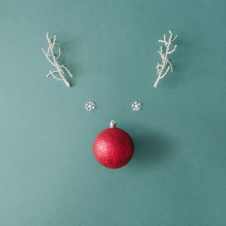 Santas reindeer made with Christmas bauble decoration and white snowy winter branches. Minimal flat lay Christmas concept.