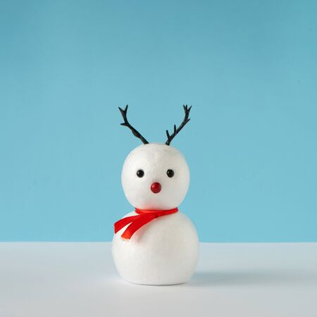 Snowman on bright blue background with reindeer nose and antlers. Winter holiday concept. Christmas minimal idea. Standard-Bild - 135471523