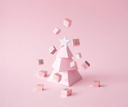 Christmas composition. Pink Christmas tree, with presents on pink background. Happy holidays. new year minimal concept. Standard-Bild - 135471726