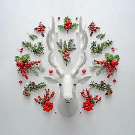 Christmas flat lay layout with Santa deer and natural decoration. Creative Holiday concept. Reindeer minimal background.