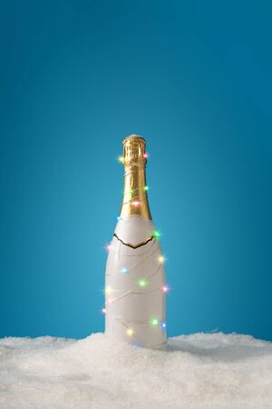 Champagne bottle with Christmas tree light decoration with snow. Minimal New Year party creative concept. Standard-Bild - 135472572