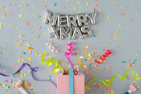 Creative composition made with gift box and party streamers on pastel grey background. Christmas party flat lay concept. Standard-Bild - 135472684
