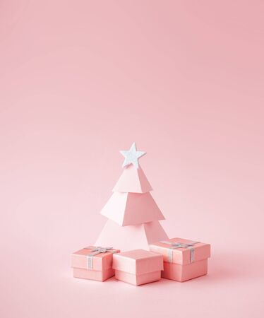 Christmas composition. Pink Christmas tree, with presents on pink background. Happy holidays. new year minimal concept.