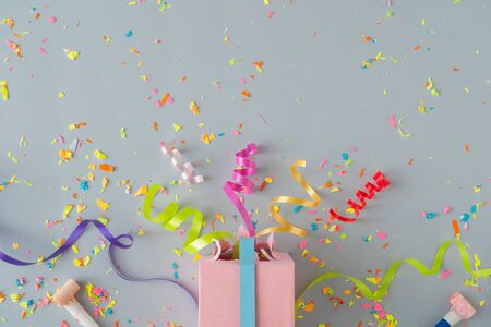 Creative composition made with gift box and party streamers on pastel grey background. Celebration party flat lay concept.