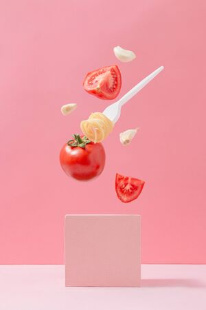 Pasta ingridients in free fall. Spaghetti, tomato and garlic against pastel pink background. Minimal food concept.