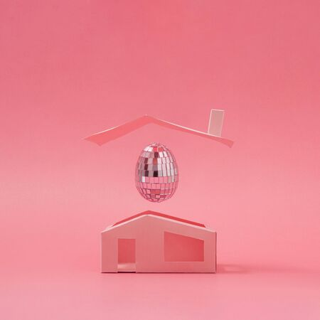 Pnk disco ball Easter egg above minimalistic house. Easter holiday creative concept background.