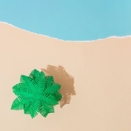 Tropical palm tree on sandy beach made of paper. Minimal summer concept. Vacation 2020 idea background.