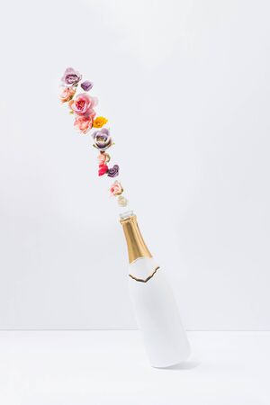 Creative concept with white champagne bottle and colorful natural spring flowers. Minimal celebration or party background.