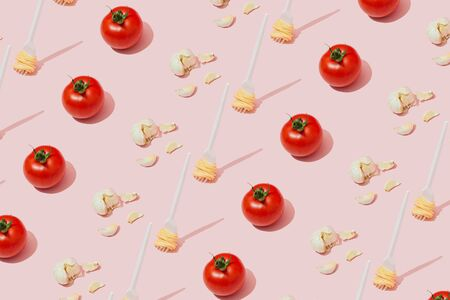Repeating collage of fork with spaghetti pasta, tomato and garlic against pastel pink background. Italian food concept. Imagens