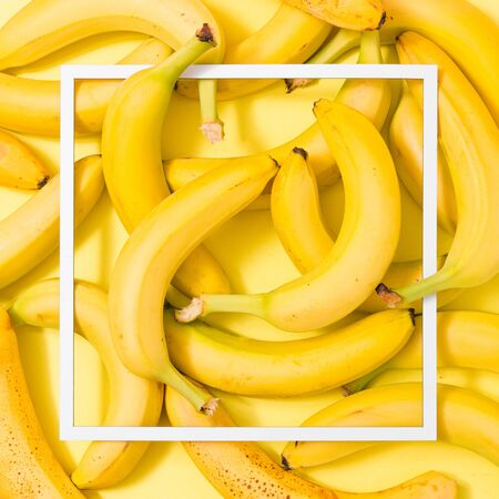 Creative layout made of bananas on yellow background with paper card note. Flat lay. Fruit concept. Food layout. Imagens