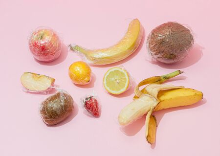 Creative layout made of fruit wrapped in stretch wrap plastic on pink background. Minimalistic arrangement. Fruit concept. Food layout.