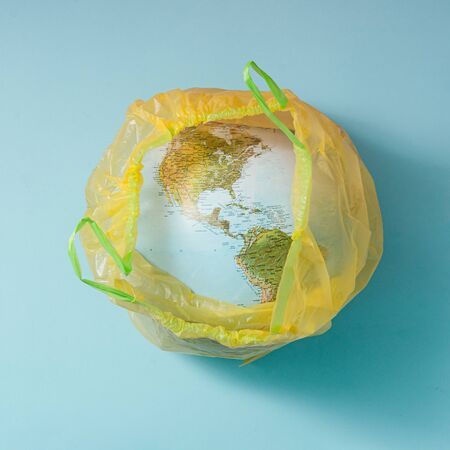 Creative concept wit planet Earth in plastic trash bag. Minimal flat lay.