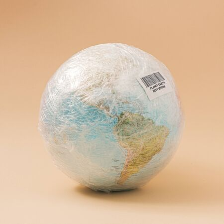 Planet Earth in stretch wrap plastic with best before sticker. Minimal enviromental concept. Imagens