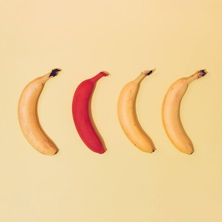 Four bananas against yellow background, one painted in red. Minimal tropical fruit concept.