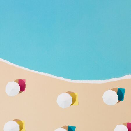 Colorful minimalistic sandy beach and sea made out of paper. Beach umbrellas and towels. Summer vacation background concept. Imagens
