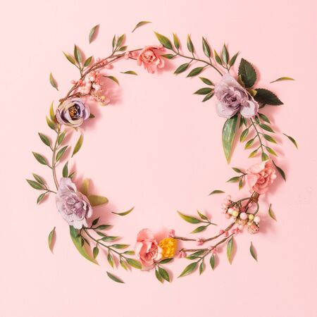 Creative spring layout made with colorful flowers and green leaves on pastel pink background. Minimal summer nature concept. Flat lay.