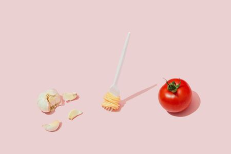 Minimal food concept with fork with spaghetti pasta, tomato and garlic against pastel pink background. Imagens