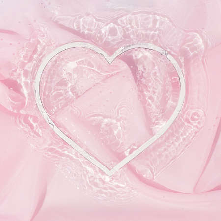Heart shape copy space in water with silk fabric. Valentines or woman's day background design. Minimal flat lay nature.