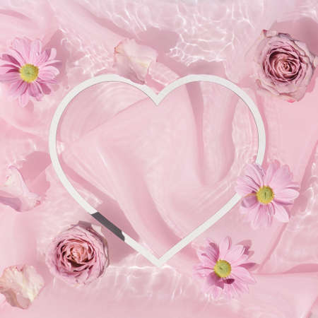 Pink rose flowers in water with silk fabric and heart shape copy space. Valentines or woman's day background design. Minimal flat lay nature.