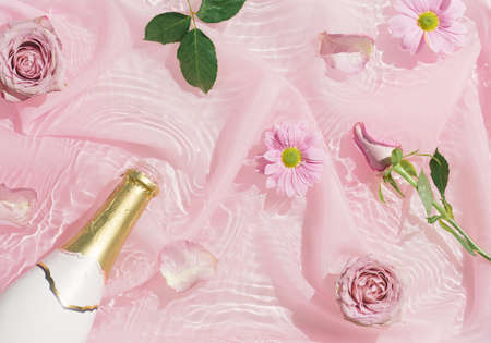 Pink rose flowers in water with silk fabric and champagne bottle. Valentines or woman's day background design. Minimal flat lay nature.