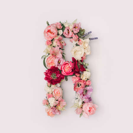 Letter R made of real natural flowers and leaves. Flower font concept. Unique collection of letters and numbers. Spring, summer and valentines creative idea.
