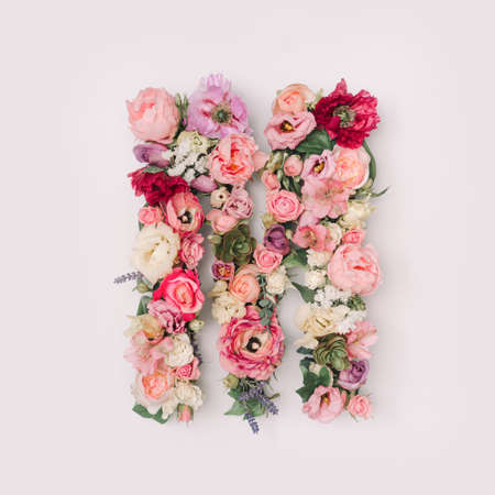Letter M made of real natural flowers and leaves. Flower font concept. Unique collection of letters and numbers. Spring, summer and valentines creative idea. 版權商用圖片