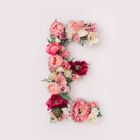 Letter E made of real natural flowers and leaves. Flower font concept. Unique collection of letters and numbers. Spring, summer and valentines creative idea.