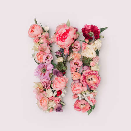 Letter W made of real natural flowers and leaves. Flower font concept. Unique collection of letters and numbers. Spring, summer and valentines creative idea.