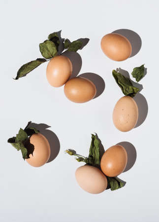 2021 Easter real unique still life composition. Eggs with dry natural leaves. Flat lay minimal background. 版權商用圖片