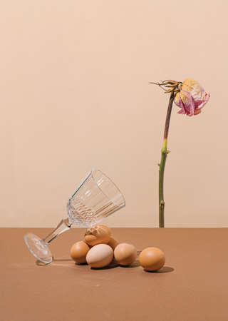 2021 Easter real unique still life composition. Eggs with beautiful dry flower and champagne glass. Creative retro minimal background.