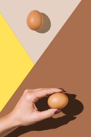 2021 Easter real unique still life composition. Eggs with beautiful woman hand. Flat lay minimal background.