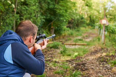 hunter man: Man shoot with air rifle. Stock Photo