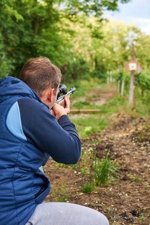 hombre disparando: disparar hombre con rifle de aire comprimido.