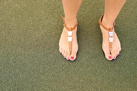 Sandálias nos pés das mulheres.