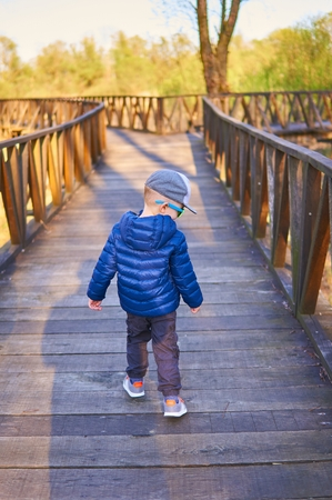 Young boy staying on wooden bridge. Autumn fashion. 版權商用圖片