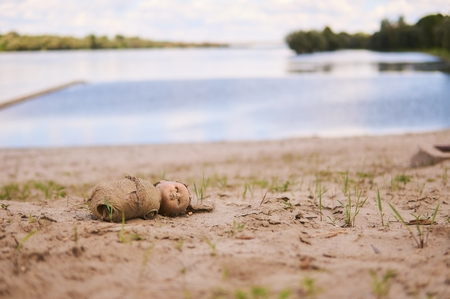 Doll on sand near river.