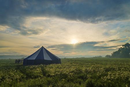 霧深い夢の風景に大きなテントの近くの人々