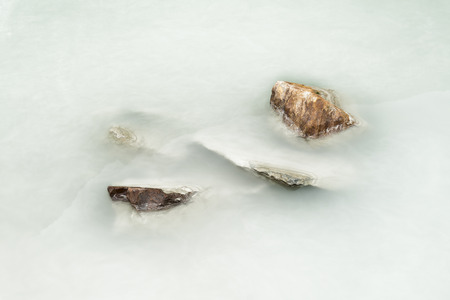 silty: Stones in silty water Stock Photo